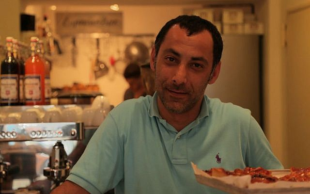 Iranian refugee Reza Dayeenavi at his cafe, Espresso Bar. (Micki Weinberg/The Times of Israel)