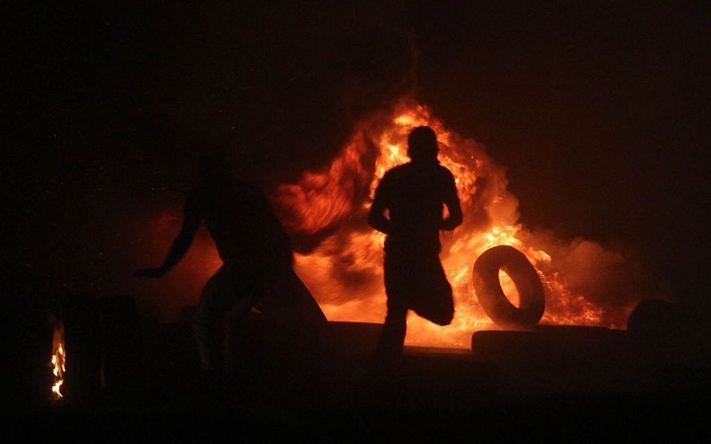 Palestinian men burning tires during clashes with Israeli border police at the Qalandiya checkpoint, between Jerusalem and Ramallah, late on July 24, 2014, following a massive march attended by 10,000 Palestinian protesters against Israel's military offensive in the Gaza Strip. (photo credit: Issam Rimawi/FLASH90)