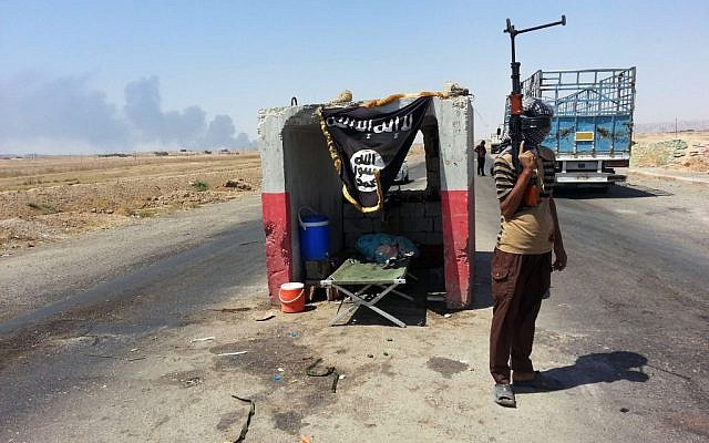 In this file photo taken Thursday, June 19, 2014, an al-Qaeda-inspired militant stands guard at a checkpoint captured from the Iraqi Army outside Beiji refinery, some 250 kilometers (155 miles) north of Baghdad, Iraq. (photo credit: AP Photo, File)