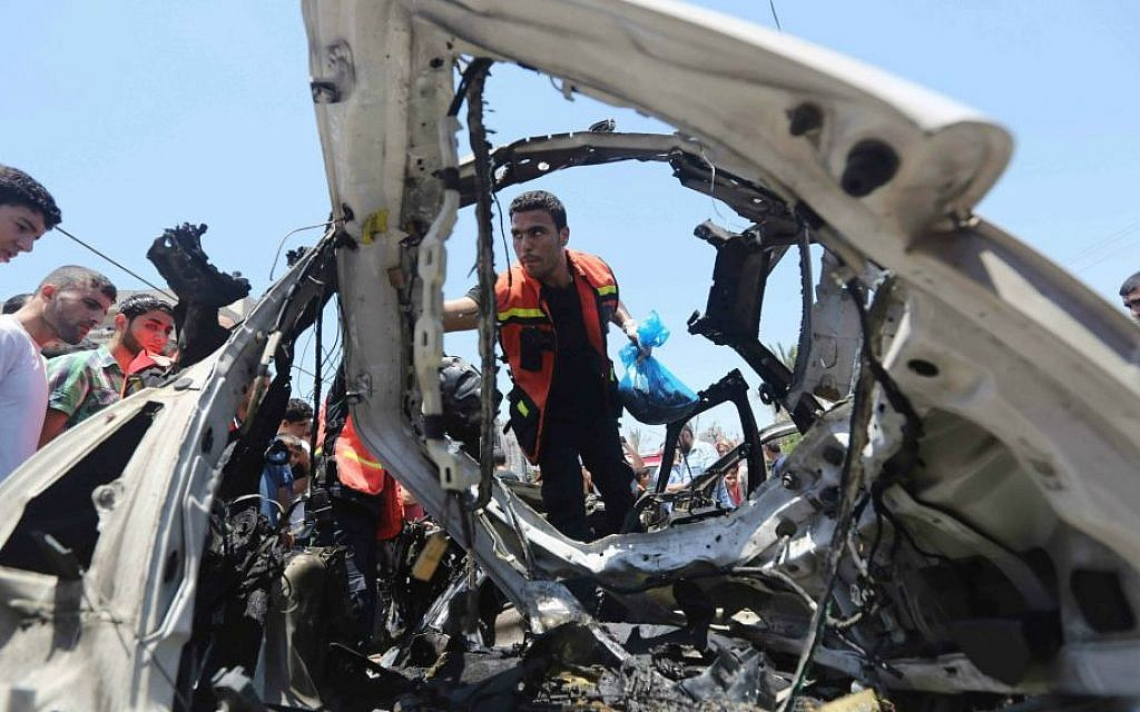 Palestinians gather around a car wreckage after an airstrike in Jabalya refugee camp in the north of the Gaza Strip, Thursday, July 10, 2014. (AP Photo/Hatem Moussa)