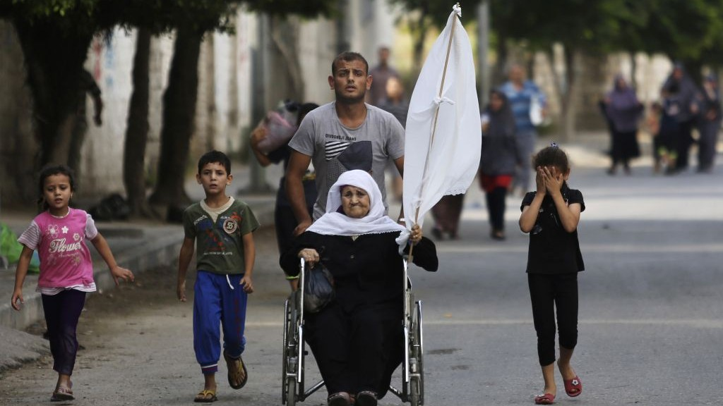 A Palestinian man wheels an elderly woman holding a white flag forward as they flee their homes in the Shejaiya neighborhood of Gaza City, in the northern Gaza Strip, Sunday, July 20, 2014. (AP Photo/Hatem Moussa)