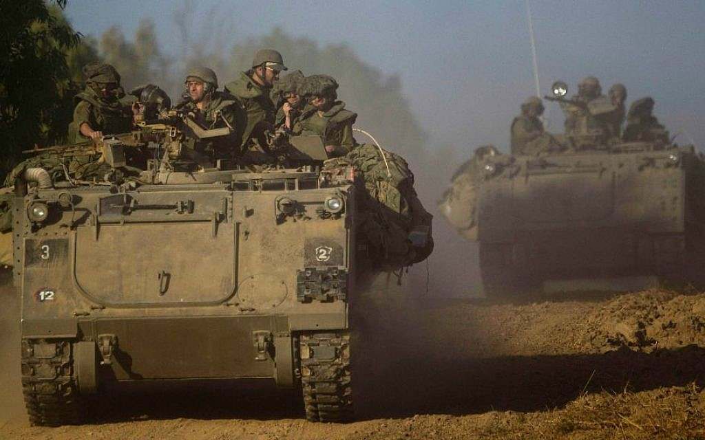 Israeli soldiers drive an armored personnel carrier to a position near the Israel Gaza border, Thursday, July 10, 2014. (AP Photo/Ariel Schalit)