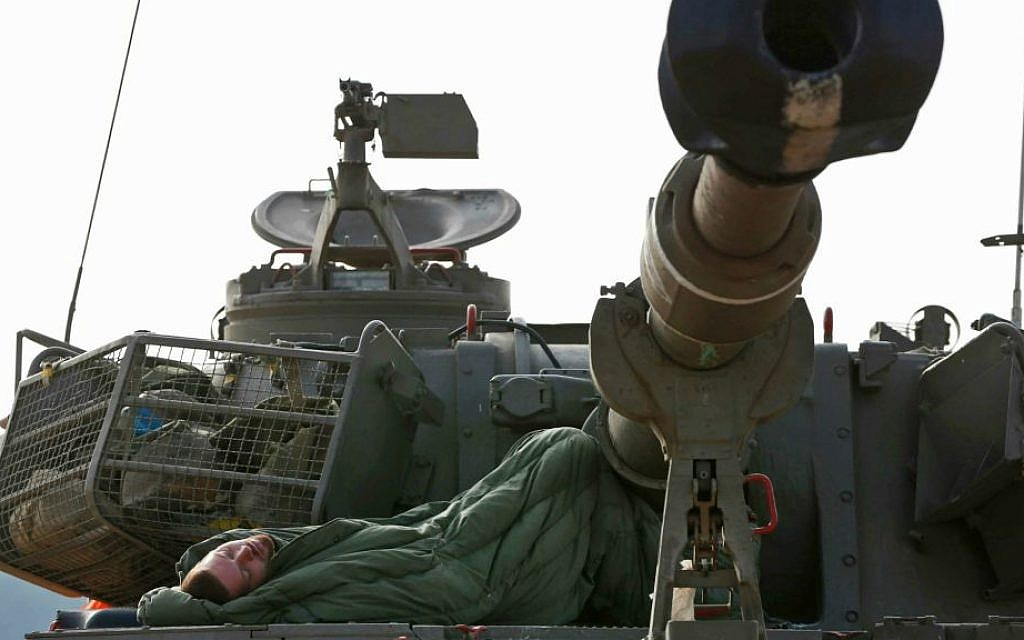 An Israeli soldier sleeps on a mobile artillery unit at a position on the Israel-Gaza border, Friday, July 11, 2014. (AP Photo/Lefteris Pitarakis)