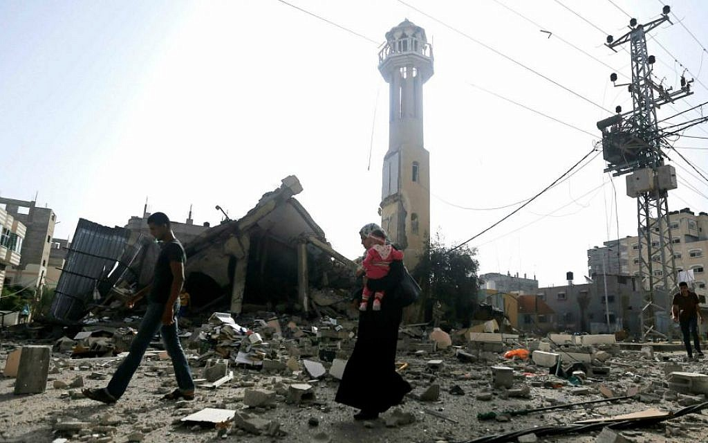 Illustrative photo of Palestinians walking past the ruins of a mosque after that was hit by an Israeli missile strike, in the central Gaza Strip (AP Photo/Hatem Moussa)