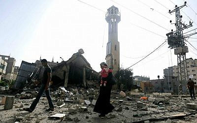 Palestinians walk past the ruins of the Al-Tawfeeq mosque after it was hit by an Israeli missile strike in the Nuseirat refugee camp, central Gaza Strip, Saturday, July 12, 2014. (AP Photo/Hatem Moussa)