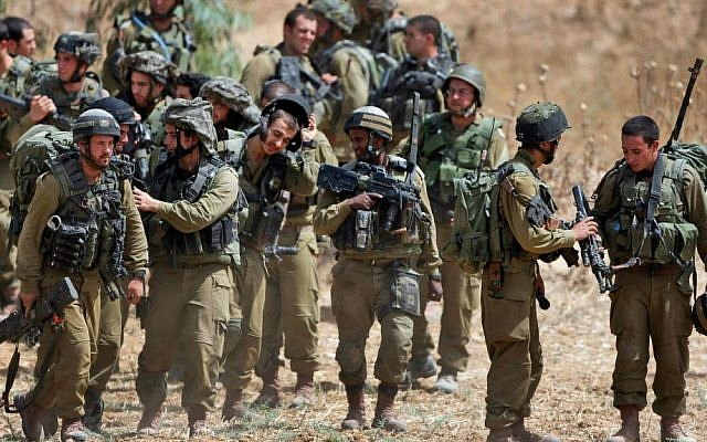 Israeli infantry soldiers get ready to walk to their armored personnel carriers to take up new positions on the Israel-Gaza border, Saturday, July 12, 2014. (AP Photo/Lefteris Pitarakis)