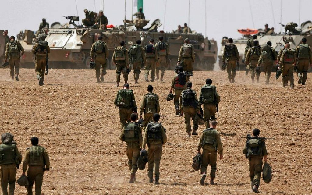 Israeli infantry soldiers walk to their armored personnel carriers to take up new positions on the Israel-Gaza border, Saturday, July 12, 2014. (AP Photo/Lefteris Pitarakis)