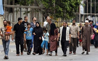 Palestinians who fled their homes in the Shejaiya neighborhood, arrive in Gaza City,  Sunday, July 20, 2014. Hundreds of panicked residents have fled the neighborhood which they say has come under heavy tank fire from Israeli forces. (AP Photo/Lefteris Pitarakis)