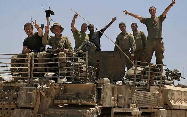 Israeli soldiers give the victory sign on the top of armored vehicle near the Israel Gaza border, Tuesday, July 29, 2014. (photo credit: AP Photo/Tsafrir Abayov)