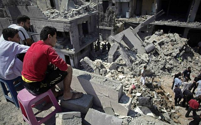 Palestinians search in the rubble of a destroyed house where eight members of the al-Haj family were killed in a strike early morning in Khan Yunis refugee camp, southern Gaza Strip, on Thursday, July 10, 2014. (photo credit: AP/Khalil Hamra)