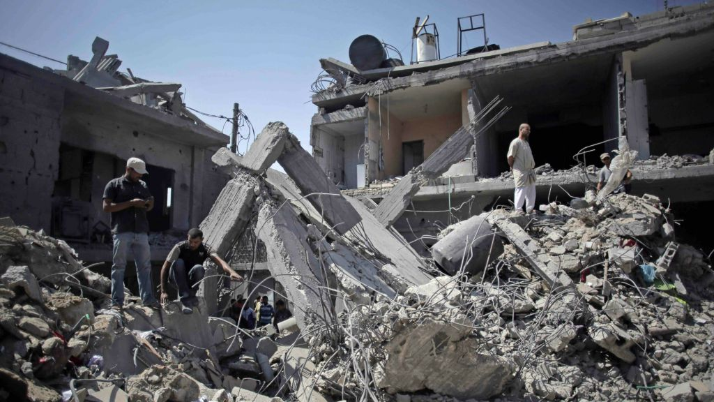 Palestinians search in the rubble of a destroyed house where eight members of the Al Haj family were killed in a strike early morning in Khan Younis refugee camp, southern Gaza Strip on Thursday, July 10, 2014. (AP Photo/Khalil Hamra)