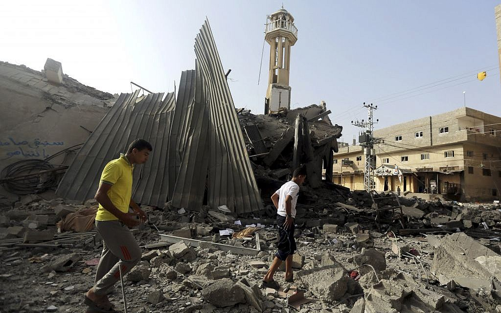 Palestinians gather around the ruins of the Al-Tawfeeq mosque after it was hit by an Israeli missile strike in the Nuseirat refugee camp, central Gaza Strip, Saturday, July 12, 2014. Israeli airstrikes overnight targeting Hamas in Gaza hit the mosque, which Israel said concealed weapons. (photo credit: AP Photo/Hatem Moussa)