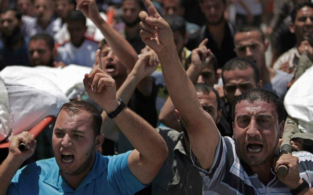 Palestinian mourners chant slogans as they carry the bodies of eight members of the Al Haj family, who were killed in an Israeli missile strike early morning, during their funeral in Khan Younis refugee camp, southern Gaza Strip on Thursday, July 10, 2014. (AP Photo/Khalil Hamra)