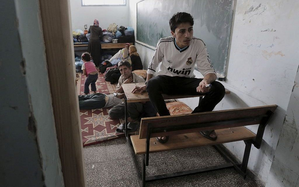 Palestinians take shelter at a United Nations school after having fled their homes in Gaza,  July 13, 2014 (photo credit: AP/Adel Hana)