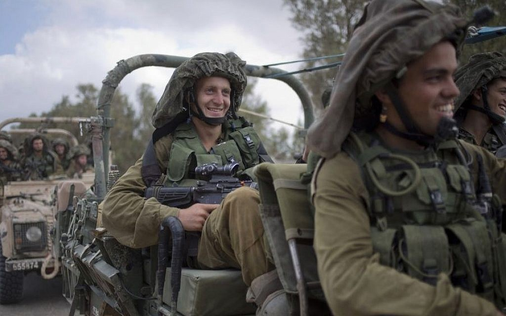 IDF soldiers smile as they ride on a military vehicle near the Israel-Gaza Border, Thursday, July 17, 2014. (Photo credit:AP/Ariel Schalit)