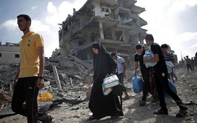 Palestinians pass by destroyed houses after they salvage usable things in their belongings found at their destroyed houses during a 12-hour cease-fire in Gaza City's Shejaiya neighborhood, Saturday, July 26, 2014.  (Photo credit: AP/Khalil Hamra)
