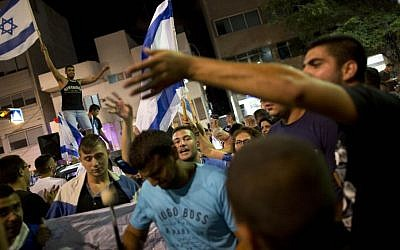 In this file photo taken Saturday, July 19, 2014, an Israeli right-wing activist waves the Israeli flag in support of Israel's operation in Gaza, during a demonstration in Tel Aviv, Israel. (Photo credit: AP/Oded Balilty)