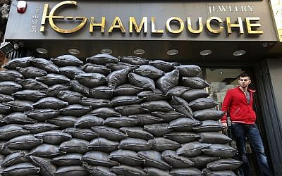 In this Tuesday, Jan. 28, 2014, file photo, a Lebanese man walks past sand barriers that were set in front of jewelry shop in a Shiite neighborhood in a southern suburb of Beirut. (photo credit: AP/Hussein Malla, File)