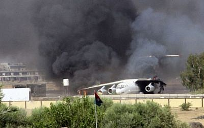 In this Saturday, July 26, 2014 screenshot from video obtained from a freelance journalist traveling with the Misarata brigade, shows an airplane on the tarmac of the airport belching black smoke into the air during fighting between the Islamist Misarata brigade and a powerful rival militia, in Tripoli, Libya.  (photo credit: AP/AP video)