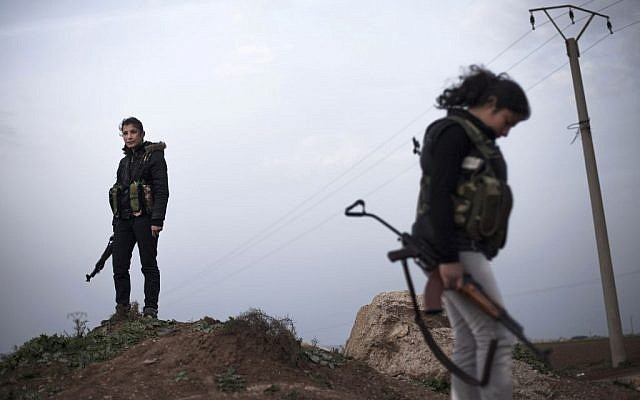 Kurdish female members of the Popular Protection Units stand guard at a check point near the northeastern city of Qamishli, Syria, March 3, 2013. (AP/Manu Brabo)