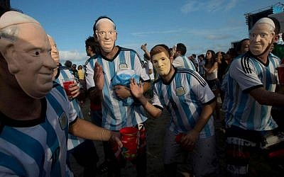 Soccer fans of the Argentina national soccer team wear masks with faces of Pope Francis and Argentine soccer player Lionel Messi during a live telecast in July of the soccer World Cup semifinal match between Argentina and Netherlands, inside the FIFA Fan Fest area on Copacabana beach, in Rio de Janeiro, Brazil. (AP Photo/Silvia Izquierdo, File)