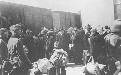 This handout photo provided by the United States Holocaust Memorial Museum shows Aleksander Belev, center, facing camera, the Bulgarian Commissioner for Jewish Questions, overseeing the deportation of Macedonian Jews from Bulgarian-occupied Skopje, Yugoslavia, in March 1943. (AP Photo/Central Zionist Archives via the United States Holocaust Memorial Museum)