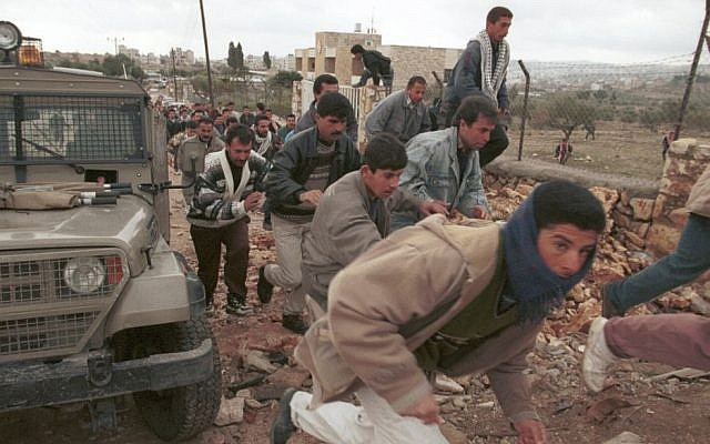 Palestinian men run through a checkpoint in Bethlehem, where they have been stopped by Israeli soldiers on their way to Friday prayers at the Temple Mount in Jerusalem's Old City,  January 31, 1997 photo credit: Nati Shohat/Flash90)