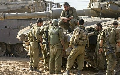 Israeli soldiers next to a Merkava tank stationed at an army deployment area near Israel's border with the Gaza Strip, on July 24, 2014. (photo credit: AFP/Jack Guez)