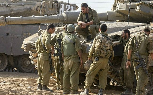 Israeli soldiers next to a Merkava tank stationed at an army deployment area near Israel's border with the Gaza Strip , on July 24, 2014 (photo credit: AFP/ Jack Guez)