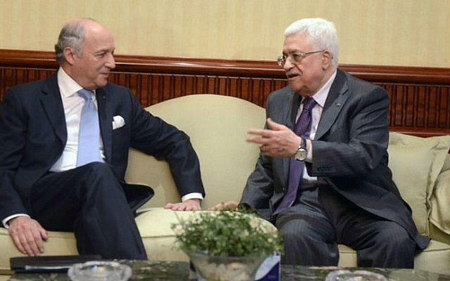 A handout picture released by the Palestinian president's office (PPO) shows Palestinian leader Abbas (R) meeting with French Foreign Minister Laurent Fabius ahead of a meeting in Cairo on July 18, 2014 (photo credit: AFP/PPO/Thaer Ghanem)