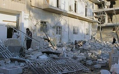 This photo taken on Wednesday, June 25, 2014, and provided by the anti-government activist group Aleppo Media Center (AMC), which has been authenticated based on its contents and other AP reporting, shows Syrians inspecting the rubble of a damaged houses following a Syrian government airstrike in Aleppo, Syria (photo credit: AP Photo/Aleppo Media Center AMC)