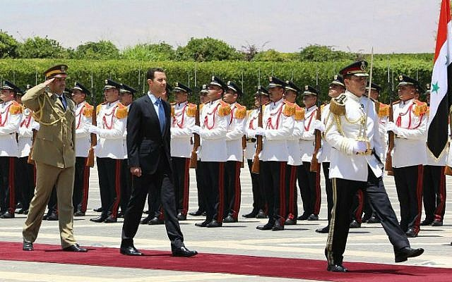 A handout picture released on the official Facebook page of the Syrian Presidency shows Syrian President Bashar Assad (C) arriving for a swearing-in ceremony on July 16, 2014 at the presidential palace in Damascus (photo credit: AFP / HO / The official page of the Syrian presidency)