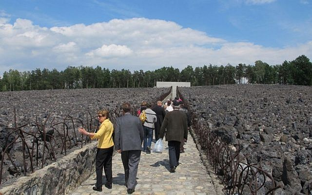 Participants in the ceremony marking the 10th anniversary of the memorial at the Belzec death camp walk through the field of slag toward the memorial wall. (Ruth Ellen Gruber/JTA)