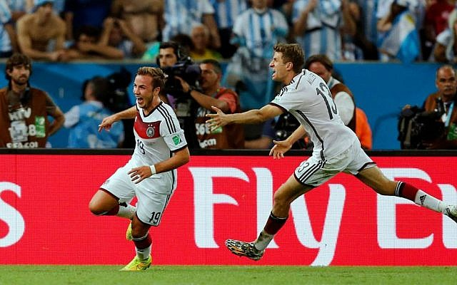Germany's Mario Goetze, left, celebrates with Thomas Mueller after scoring the winning goal during the World Cup final soccer match between Germany and Argentina at the Maracana Stadium in Rio de Janeiro, Brazil, Sunday, July 13, 2014.  (photo credit: AP/Frank Augstein)