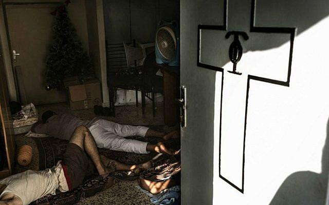 Displaced Palestinians sleep on the floor inside Gaza City's Greek Orthodox church on July 23, 2014 (photo credit: AFP/Marco Longari)_