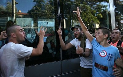 Right wing Jewish teenagers wearing stickers that say 'Kahana was right' and 'Revenge' seen giving the finger and yelling at Arab women sitting inside the tram in central Jerusalem during a large right wing protest against Arab terrorism, July 1, 2014, in response to the kidnap and murder of three Jewish teens (Nati Shohat/Flash90)
