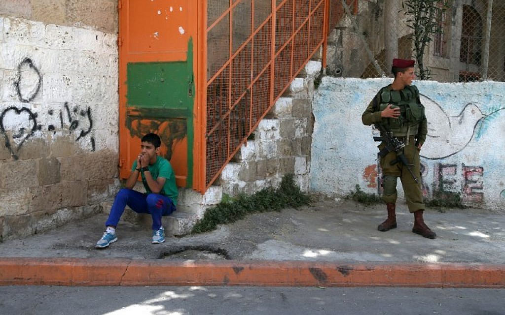 A Palestinian boy sits near Israeli soldiers deployed in the divided West Bank city of Hebron, on the first Friday of the Muslim month of Ramadan. July 04, 2014. (Photo credit: Nati Shohat/FLASH90)