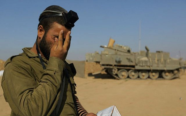 An Israeli soldier prays at an IDF staging area near the Israeli border with Gaza, on July 31, 2014 (photo cropped: Yaakov Naumi/FLASH90)