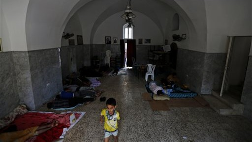 Palestinians start their day on the grounds of the St. Porphyrios Church in Gaza City where many Palestinians have sought refuge from the war, on Wednesday, July 23, 2014. (photo credit: AP Photo/Lefteris Pitarakis)
