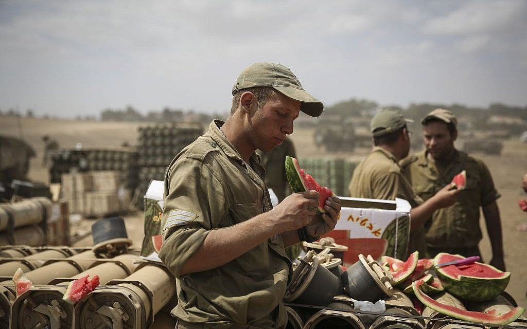 Israeli soldiers eat watermelon from the truckload they had received from Israeli supporters, in a gathering point in a field near the Israeli border with Gaza, on July 25, 2014. (photo credit: Hadas Parush/FLASH90)