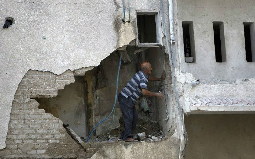 A Palestinian man inspects the damage in a building that was partially destroyed following an Israeli air strike on July 19, 2014, in Gaza (photo credit: AFP/ Mahmud Hams)