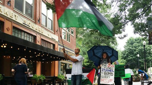 Ahmad Abuleil waves a Palestinian flag as he leads Amira Sakalla, head of University of Tennessee Students for Justice In Palestine, and others in a march in Knoxville, Tenn. on Friday, July 18, 2014 (AP/Knoxville News Sentinel, Megan Boehnke)
