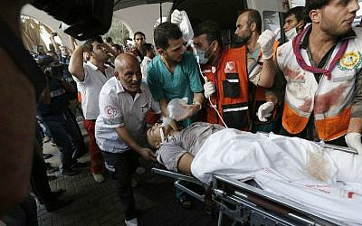 Palestinian paramedics carry a man wounded in a strike at a marketplace in the Shejaiya neighborhood, as he arrives at a hospital in Gaza City on Wednesday, July 30, 2014 (photo credit: AFP/ Mohammed Abed)