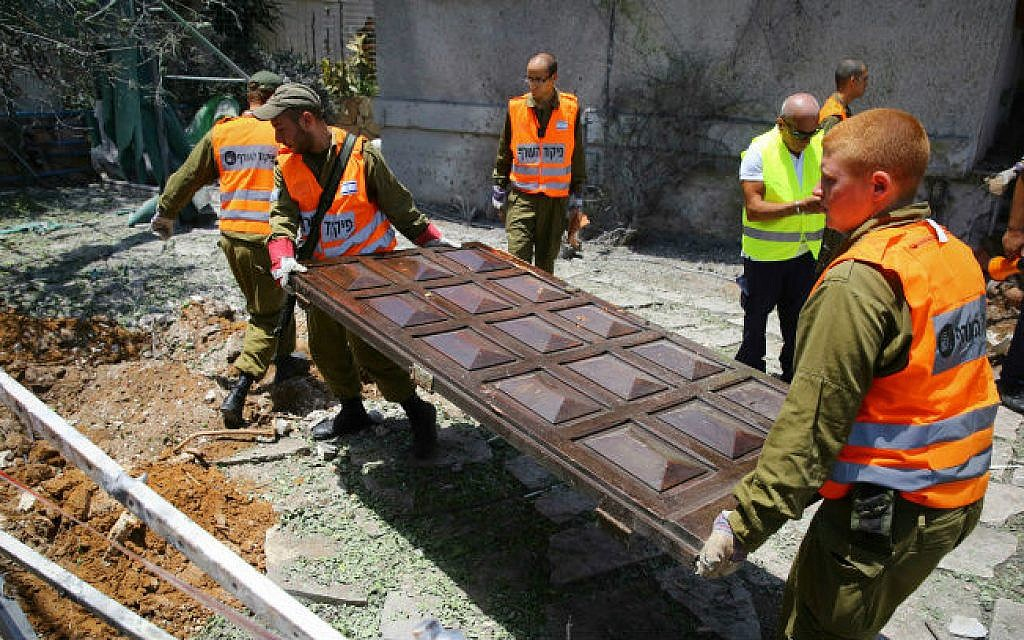 Police explosives experts and Home Front Command workers at the scene where a grad rocket fired from Gaza hit a house in the Israeli city of Ashdod, on July 15, 2014 (photo credit: Flash90)