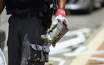 A police officer holds the remains of a grad rocket, in the Israeli city of Ashdod, on July 15, 2014 (photo credit: Flash90)