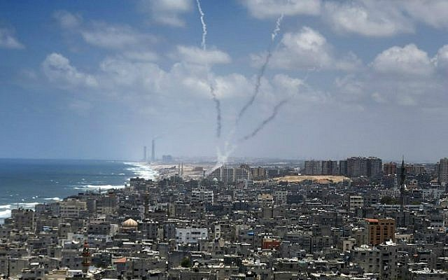 Smoke from rockets fired from near Gaza City is seen after being launched toward Israel, on July 15, 2014. (photo credit: AFP/Thomas Coex)