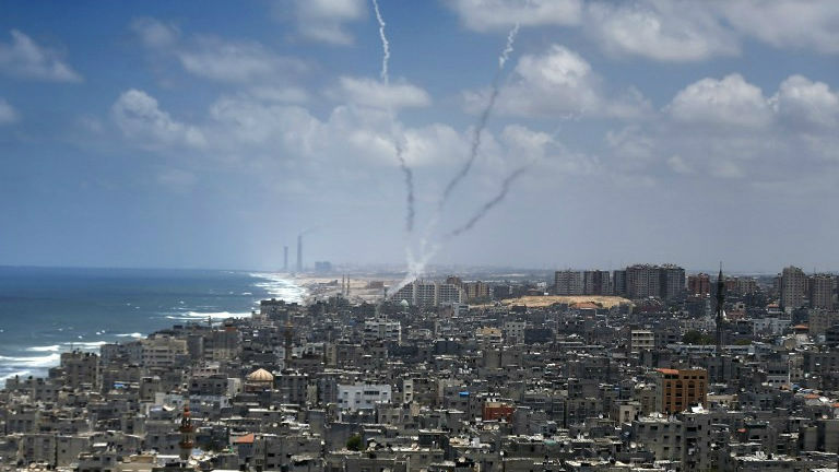 Smoke from rockets fired from near Gaza City is seen after being launched toward Israel, on July 15, 2014 (photo credit: AFP/ Thomas Coex)