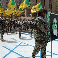 Illustrative: Iraqi Hezbollah members hold up the yellow flags of the Iraqi branch of the Lebanese terror group and a portrait of Iran's late supreme leader, Ayatollah Ruhollah Khomeini, as they walk on an Israeli flag painted on the ground during a parade marking al-Quds (Jerusalem) International Day on July 25, 2014, in the Iraqi capital Baghdad. (AFP/Ali al-Saadi)