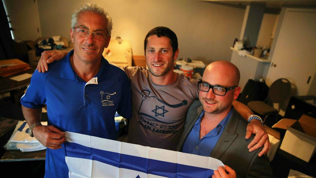 Israel Lacrosse head coach Bill Beroza, left, attack-man Noach Milller, center, and team executive director Scott Neiss hold an Israeli flag inside a hotel room used to organize team gear, July 15, 2014, Commerce City, Colo. (photo credit: AP/Brennan Linsley)