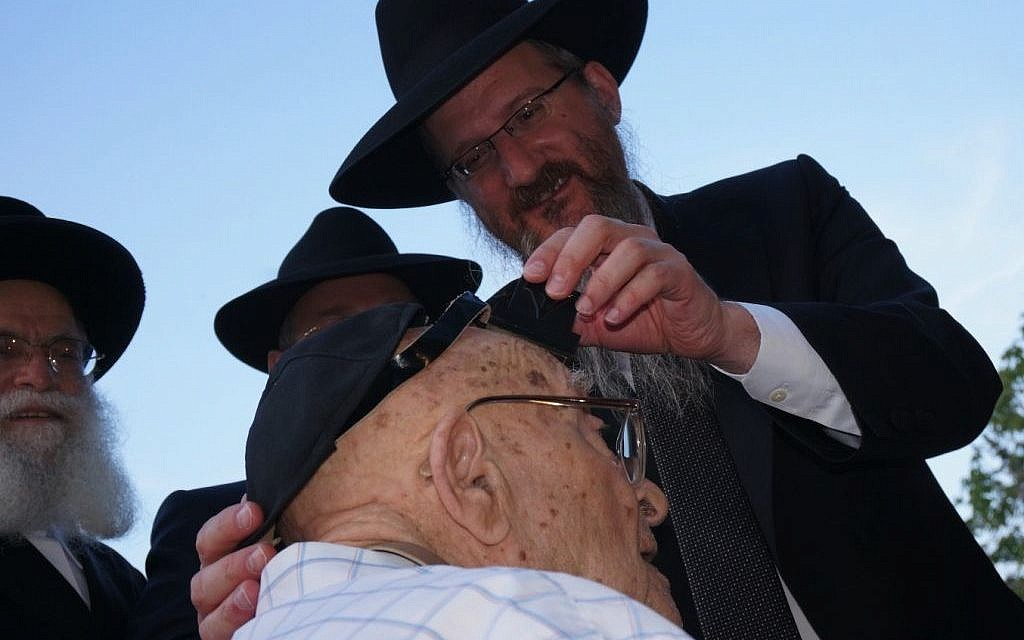Russian Chief Rabbi Berel Lazar putting teffilin on 102-year old David Barulya, a World War II veteran and Crimean Holocaust survivor, at a Holocaust commemoration ceremony in Sevastopol, July 10, 2014. (Cnaan Liphshiz/JTA)